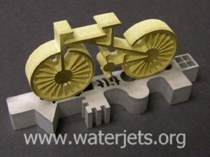 Brass bicycle and test part cut on a waterjet with a tilting nozzle
